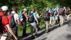 Mit der Fahne der Schweizerischen Chorvereinigung im Gepäck legt die Wandergruppe Kilometer um Kilometer zurück.