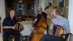 Drei Musikanten, die in fröhlicher Rund mit Schwyzerörgeli und Kontrabass in einer Küche musizieren.