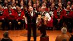 Der Solojodler und der Schwyzerörgeler stehen vor den Sängern in roten Hemden, die im Halbkreis sitzen.