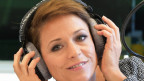 Michelle im Studio der SRF Musikwelle fasst sich an den Kopfhörer und lächelt Moderator Leonard an.