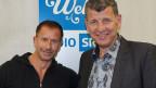 Moderator und Gast vor dem blau-weissen Logo der SRF Musikwelle.