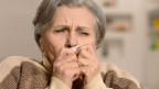 Eine Frau hält sich kurz vor dem Niesen ein Taschentuch vor die Nase.