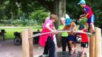 Grosseltern und Enkel trainieren ihr Gleichgewicht auf einem Gerät im Schützenmattpark.