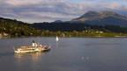 Ein Dampfschiff in der Abenddämmerung auf dem See.