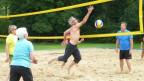 Beachvolleyballspieler hechtet Ball übers Netz.