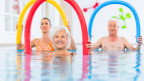 Zwei Frauen und ein Mann machen mit Schaumstoffröhren Übungen in einem Wasserbecken.