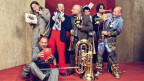 Die sieben Musiker mit Torte, Ballon, Papierschlangen und Champagner in Festlaune.