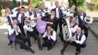 Eine Dirigentin umgeben von Musikanten, die auf ihren Instrumenten gespielt übermütig spielen.