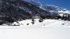 Blick auf das verschneite Dorf mit Kirche.