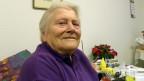 Die Rentnerin trägt einen lila Pullover und sitzt in einem Stuhl vor einem Bett mit einer mehrfarbigen Wolldecke.