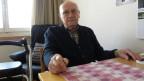 Der Rentner sitzt am Tisch in seiner Alterswohnung.
