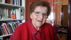 Die Seniorin trägt eine rote Bluse unter einer roten Strickjacke und sitzt vor einem Bücherregal.