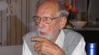 Fernand Rausser mit grauem Haarkranz, grauem Bart und Brille beim Interview.