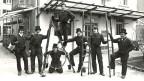 Sieben Kaminfeger mit Leiter und Handwerkutensilien auf einem Gruppenfoto.