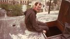 Der Kaminfeger sitzt auf dem Dach vor einer offenen Luke.