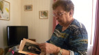 Die Seniorin steht im Wohnzimmer und blättert in einem alten Fotoalbum.