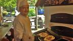 Ein Koch vor einem offenen Ofen.