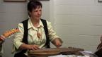 Eine dunkelhaarige Frau spielt Zither.