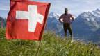 Jodelnder Mann auf Anhöhe neben Schweizerfahne im Hintergrund Berge.