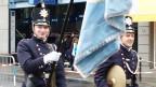 Ein Fahnenträger in einer blauen Uniform.