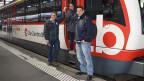 Drei Personen, die vor der Tür eines Zugwagens stehen.
