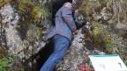Der Reporter steht vor einem Felsen, der eine breite Spalte aufweist.