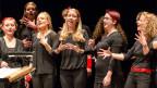 Sänger und Sängerinnen in schwarzer Kleidung mit roten Accessoires.