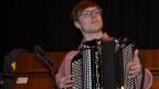 Ein junger Akkordeonist, der in sein Spiel versunken ist.