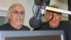 Die Amigos im Sendestudio der SRF Musikwelle hinter Mikrophonen.