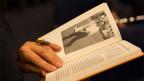 Ein aufgeschlagenes Buch in den Händen einer Frau.