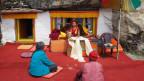 Der Lama des nepalesischen Klosters berät Frauen aus der lokalen Bevölkerung und betet mit ihnen.
