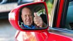 Ein älterer Autofahrer zeigt im Seitenspiegel Daumen hoch.