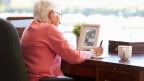 Frau sitzt an Tisch und schreibt ihre Memoiren.