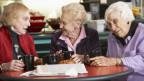 Drei Seniorinnen diskutieren beim Café.