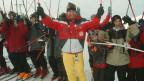 Der Bundesrat in Skiausrüstung vor einer Gruppe fröhlicher junger Burschen, ebenfalls in Skiausrüstung.