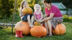 Zwei kleine Mädchen sitzen neben ihrer Grossmutter auf sehr grossen Kürbissen.