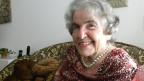 Die Seniorin trägt eine elegante Bluse und sitzt in ihrem Wohnzimmer auf einem Sofa.