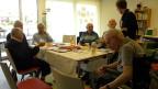 Sechs Senioren sitzen mit zwei Therapeutinnen an einem Tisch.