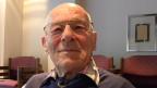 Porträt eines älteren Mannes, der in einem grossen Wohnzimmer mit heller Fensterfront sitzt.