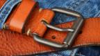Ein Gürtel aus Leder in den Schlaufen einer Jeanshose.