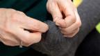 Hände einer Frau, die mit Nadel und Faden ein Loch in einer Socke flickt.