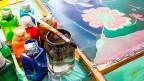Ein paar Farbdosen neben einer Seidenmalerei.