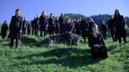 Die Sängerinnen und Sänger stehen und sitzen an einem Hang auf einer Wiese unter blauem Himmel.