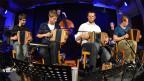 Eine mehrköpfige Musikformation auf einer Bühne.