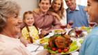 Eine Familie isst Fleisch am Tisch.