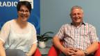 Moderatorin und Gast sitzen auf zwei roten Sesseln vor dem blau-weissen Logo der SRF Musikwelle.