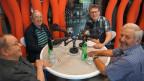 Vier Männer sitzen in einem Aufnahmestudio an einem runden Tisch vor Mikrofonen.