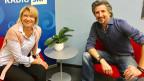 Eine blondhaarige Frau und ein dunkelhaariger Mann sitzen nebeneinander auf roten Sesseln.