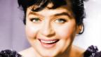 Eine junge lachende Frau mit dunklen Haaren.