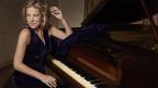 Die Musikerin sitzt im dunkelvioletten Abendkleid an einem schwarzen Flügel.